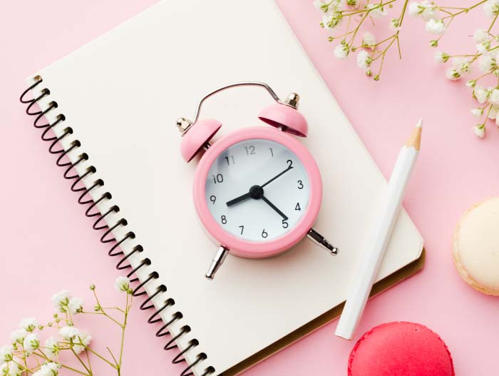 Pink clock on notepad with flowers